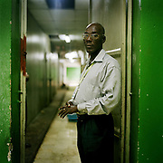 "Pierre Yves Jovin, 56, Morgue Manager, Central hospital, Port Au Prince. Pierre has worked at the morgue for 27 years. He is the manager in charge. He is standing in front of the cold stores each of which hold about 60 bodies. Relatives are still coming to see if they can identify their loved ones such is the need to know if their families are just missing or dead.  People are searching high and low for loved ones even knowing that the chances of finding them dead or alive must be miniscule when so many have been cleared into mass graves or burnt where they lay. ""After the earthquake, all the bodies were piled outside this morgue. There was a huge pile of two to three thousand and inside there were bodies piled up to the ceiling.  Every time the earth trembled, the after-shocks caused the bodies to move and I could smell the dead"""