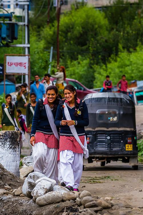 School girls walking along a road in Manali, Himachal Pradesh, India.