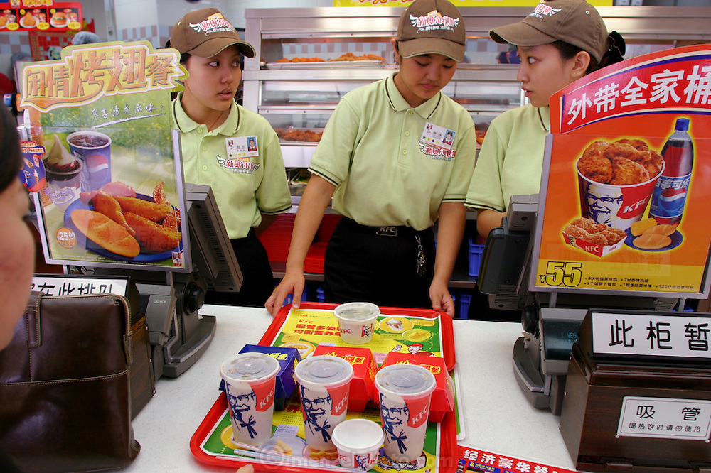 """A newer common sight is the long line of younger or newly affluent urbanites ending at the cash register of the biggest Western fast-food chain in China; their choice, on the left, is the """"Leisurely Fried Wings Meal."""" More than a hundred KFC outlets operate in Beijing alone. Hungry Planet: What the World Eats (p. 78). This image is featured alongside the Dong family images in Hungry Planet: What the World Eats."""
