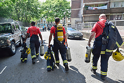 © Licensed to London News Pictures. 14/06/2017. London, UK.   A relief fire crew arrives.  The Grenfell Tower near Latimer Road in west London was engulfed in a huge fire the previous night, resulting in at least twelve fatalities with many more in critical condition. Photo credit : Stephen Chung/LNP