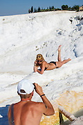 Tourists taking pictures at Pamukkale. The hard, white mineral deposits, which from a distance resemble snow, are caused by the high mineral content of the natural spring water which runs down the cliff and congregates in warm pools on the terraces. This is such a popular tourist attraction that strict rules had to be established in order to preserve its beauty, which include the fact that visitors may no longer walk on the terraces. Those who want to enjoy the thermal waters, however, can take a dip in the nearby pool, littered with fragments of marble pillars.