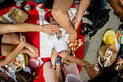 """A pic nic was held on the street in the center of Brussels, to """"reclaim the streets and the public place"""". Hundreds picnicked to demand a carfree citycenter. The event was not officially permitted. A child is being changed his diper. this image is part of a series of 8 shot from above in wide angle focus on food"""