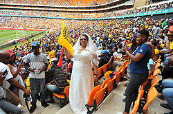 A woman in a wedding dress among hundreds of Kaiser Chiefs supporters who came in large numbers to support their team during the Soweto derby Kaizer  Chiefs and Orlando pirates for the PLS match at the FNB Stadium. Johannesburg.<br />Picture: Itumeleng English/ African News Agency /ANA