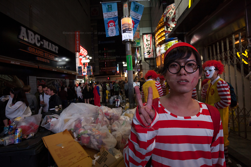 A Japanese man dressed as Wally gives a V0sign next to a huge pile of trash during the Halloween celebrations Shibuya, Tokyo, Japan. Saturday October 27th 2018. The celebrations marking this event have grown in popularity in Japan recently. Enjoyed mostly by young adults who like to dress up, drink , dance and misbehave in parts of Tokyo like Shibuya and Roppongi. There has been a push back from Japanese society and the police to try to limit the bad behaviour.