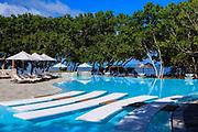 Photographie en couleur de la piscine de l'hôtel Le Shératon Déva situé à Bourail en Nouvelle Calédonie. L'image présente le passage entre les 2 bords du bassin avec des transats, des parasols, des arbres et la mer en arrière plan.