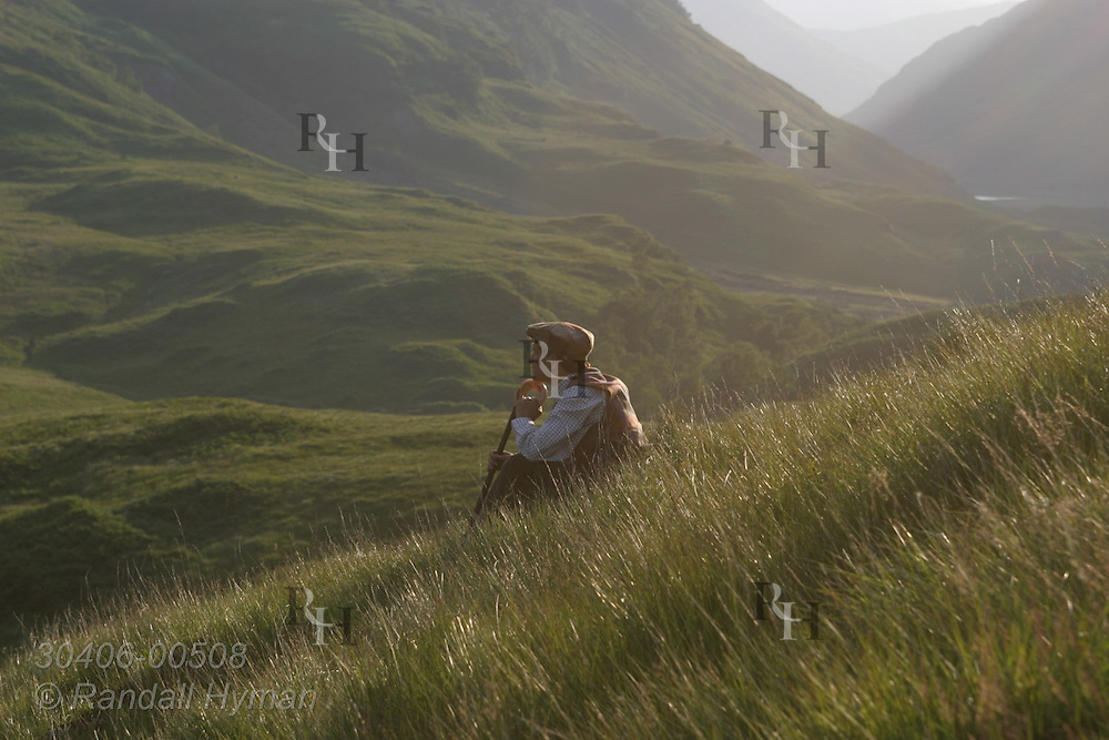 Man in traditional hiking clothes rests in grassy field of upper Glen Coe on a July afternoon; Glencoe Scotland.