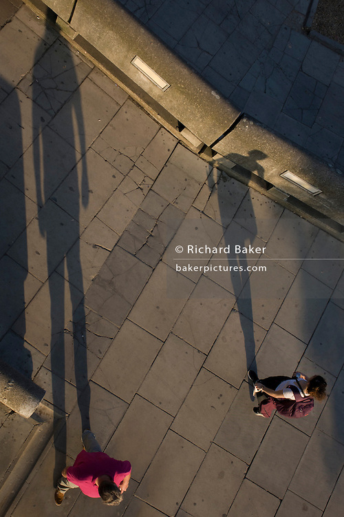 The long shadows of strangers as they pass each other on London's Southbank.