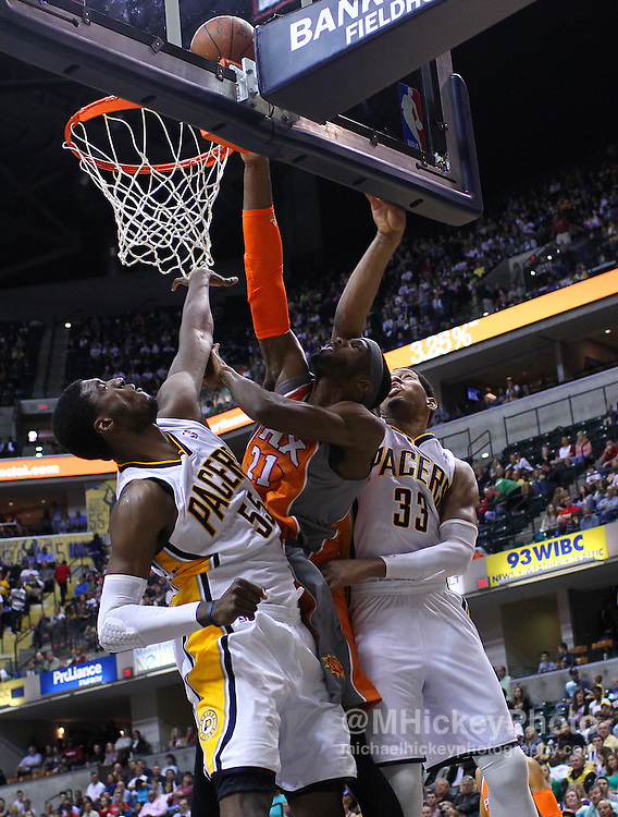 March 23, 2012; Indianapolis, IN, USA; Phoenix Suns power forward Hakim Warrick (21) shoots the ball between defenders Indiana Pacers center Roy Hibbert (55) and Indiana Pacers small forward Danny Granger (33) at Bankers Life Fieldhouse. Mandatory credit: Michael Hickey-US PRESSWIRE