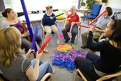 Day Service Officer and Assistant working with a Group of service users with learning disabilities using rhythm sticks during a music session,