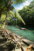 Side view of a male shirtless tourist in mid-air while diving into the Ojo De Agua natural spring, Ometepe Island, Nicaragua