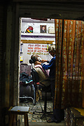 A barber shaves a client in his barbershop in Jodhpur, India