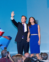 © Licensed to London News Pictures. 10/10/2012. Birmingham , UK . The British Prime Minister , David Cameron , waves to the audience and holds hands with his wife , Samantha , after delivering his closing speech to the 2012 Conservative Party Conference . Day 4 of the Conservative Party Conference at the International Convention Centre in Birmingham . Photo credit : Joel Goodman/LNP