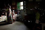As her daughter, Mahfuza Akhter (5) and son, Shakil Alom (7) look on, Shahida Begum, 35, goes about her daily household chores in her hut in Palashbari Villlage, Taragonj, Rangpur, Bangladesh on 18th September 2011, after a regular day of work as a saleswoman earning 3500 - 5000 Bangladeshi Taka per month. She is one of many rural Bangladeshi women trained by NGO CARE Bangladesh as part of their project on empowering women in this traditionally patriarchal society. Named 'Aparajitas', which means 'women who never accept defeat', these women are trained to sell products in their villages and others around them from door-to-door, bringing global products from brands such as BATA, Unilever and GDFL to the most remote of villages, and bringing social and financial empowerment to themselves.  Photo by Suzanne Lee for The Guardian
