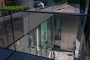 An aerial view of City workers outside corporate offices with polished, metallic architecture, on 9th June 2016, in London, United Kingdom. As a lady is in conversation on the corner, a man pushes gently on the revolving door to enter the premises while above him, another sits enjoying summer sunshine on an overhead walkway.