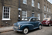 Two vintage Morris Minor 1000s parked together in a Georgian terraced street in London, United Kingdom. The Morris Minor is a British car of which more than 1.6 million were manufactured between 1948 and 1972. Initially available as a two-door saloon and tourer, or convertible, the range was expanded to include a four-door saloon. It was the first British car to sell over one million units and is considered a classic example of automotive design, as well as typifying Englishness.