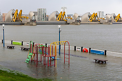 © Licensed to London News Pictures. 10/02/2020. London, UK. A children's climbing frame and benches are seen underwater during flooding at the Thames Barrier in London which is seen closed this afternoon at high tide to protect the capital from flooding during Storm Ciara. The Thames Barrier prevents the floodplain of most of Greater London from being flooded by exceptionally high tides and storm surges.  Photo credit: Vickie Flores/LNP
