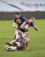 Zak Hardaker (3) of Wigan Warriors is tackled by Jack Wells (26) and Andy Ackers (9) of Salford Red Devils