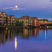 I took this picture when the full moon was shining over TRondheim and thanks to the bright nights in summer time. The water level in Nidelav (Trondheims river) was quite high.  So I got all the beautiful reflection from the houses, sky and the full moon.