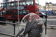 With busy traffic behind, a young window cleaner wipes a circle of soapy liquid over a City of London cafe's pane of glass.