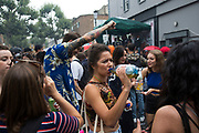 Drinking on Sunday on 28th August 2016 at Notting Hill Carnival in West London. A celebration of West Indian / Caribbean culture and Europes largest street party, festival and parade. Revellers come in their hundreds of thousands to have fun, dance, drink and let go in the brilliant atmosphere. It is led by members of the West Indian / Caribbean community, particularly the Trinidadian and Tobagonian British population, many of whom have lived in the area since the 1950s. The carnival has attracted up to 2 million people in the past and centres around a parade of floats, dancers and sound systems.