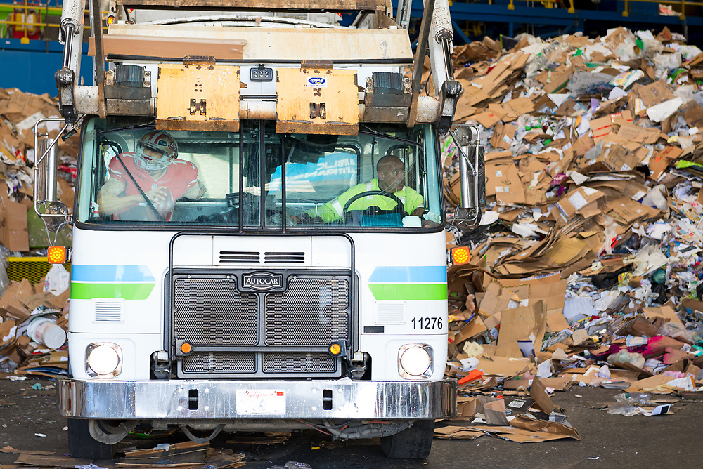 Driver empties a load of commercial recyclables on the floor of the MRF.