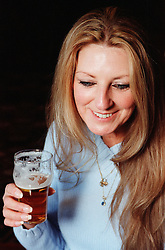Young woman holding pint of beer smiling,