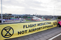 London, UK. 8 December, 2019. A banner used by climate activists from Extinction Rebellion outside Heathrow airport for a Bikes Against Bulldozers protest against Heathrow expansion and the greenwashing of climate commitments by political parties. The protest took the form of a Critical Mass bicycle ride from Hyde Park followed by a lie-in in front of a bulldozer to which Boris Johnson and John McDonnell were invited in order to fulfil their pledge of lying down in front of bulldozers to be used for Heathrow expansion.