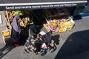 Two Musim women walk past a greengrocer selling fruit and veg and which is also advertising the transfer of money to and from abroad by Western Union, on 24th September 2021, in London, England.
