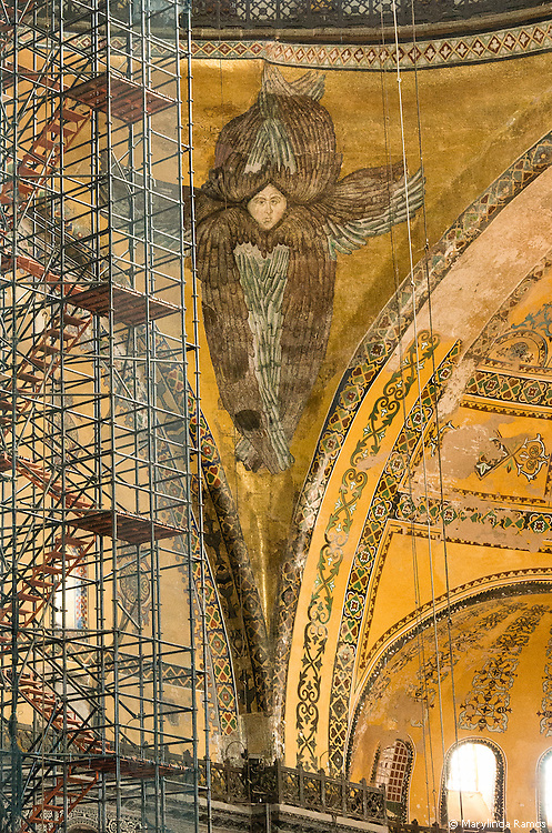 In September 2013, Aya Sofya was in the process of being restored.  Scaffolding rose from marble floor to gold-flecked domes, obscuring part of the light and much of the artwork.  IHere, a restored angel, stylistically different from mosaics elsewhere in the church, adorns a corner of the center arch.