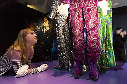 © Licensed to London News Pictures. 26/10/2017. London, UK. A curator makes adjustments outfits worn by the musician Prince during the Purple Rain period at the first ever exhibition about iconic superstar and legendary performer PRINCE showcases hundreds of never seen before artefact's directly from Paisley Park, Prince's famous Minnesota private estate. Photo credit: Ray Tang/LNP