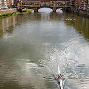 With Ponte Vecchio, the oldest and most famous bridge, serving as a background, a lone rower works his way down the River Arno in Florence, Italy.