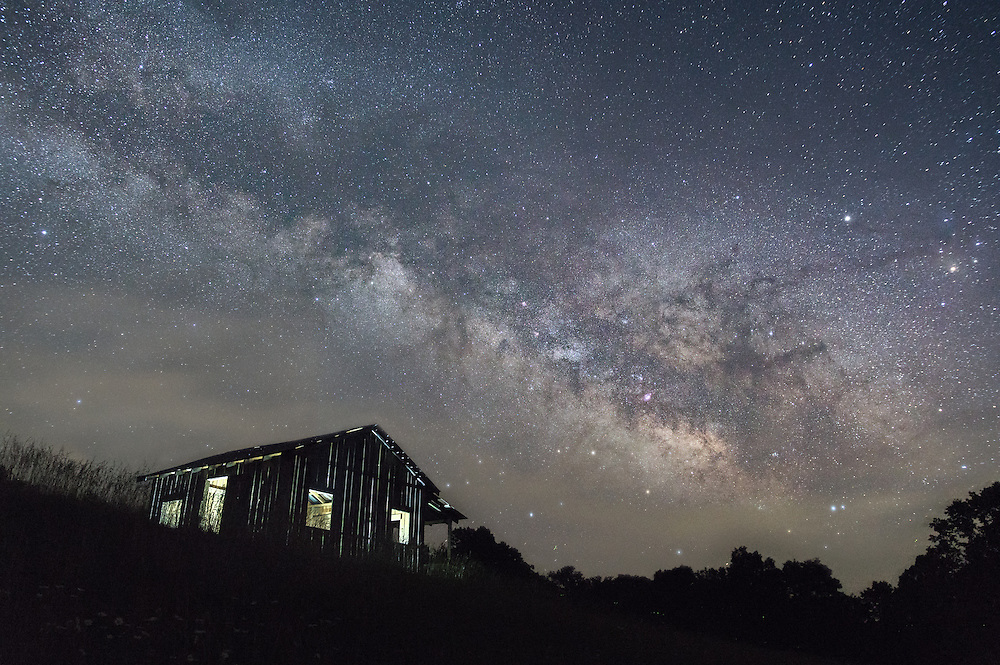 On a late Spring evening, the stars and dense Milky Way galactic core, seperated by a thin shroud of fog, loom over a landscape cloaked in shadow, lending an almost ethereal quality to the loan shack propped up by the ink shade of earth that holds it.  Calhoun County Park, West Virginia.