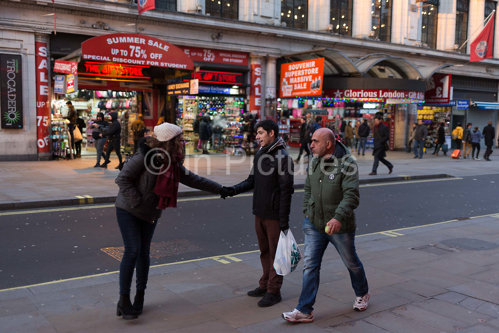 Friends reach out in the busy Coventry Street in Londons West End, on 6th February 2018, in London, England.