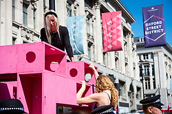 """© Licensed to London News Pictures. 25/08/2021. LONDON, UK.  Climate activists from Extinction Rebellion in Oxford Circus at a protest where people have glued themselves to a pink wooden structure.  The event is part of the 'Impossible Rebellion' protest to """"target the root cause of the climate and ecological crisis"""" and are ongoing for two weeks until the Government agrees to stop all new fossil fuel investments.  Photo credit: Stephen Chung/LNP"""