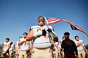 SPARTA, NJ - October 10: Jack Sylo leads his team with his traditional allegiance while holding the American Flag. Jack told me, 'I hold this flag before every game during the National Anthem to honor my late grandfather who served in the war.' <br /> <br /> We are in the midst of witnessing something this world has never experienced - a global pandemic. The coronavirus has swept away the world in March of 2020 - since then, the world we know It hasn't been the same. Jobs, businesses and futures have been put on hold and lost, yet, we have to power through to overcome one of the greatest obstacles this we have faced. The high school football season wasn't suppose to happen, but a glimmer of hope, intense safety measures & a little bit of luck has allowed for the season to start, now the question is ' Can It be completed?'<br /> <br /> Photo by Johnnie Izquierdo
