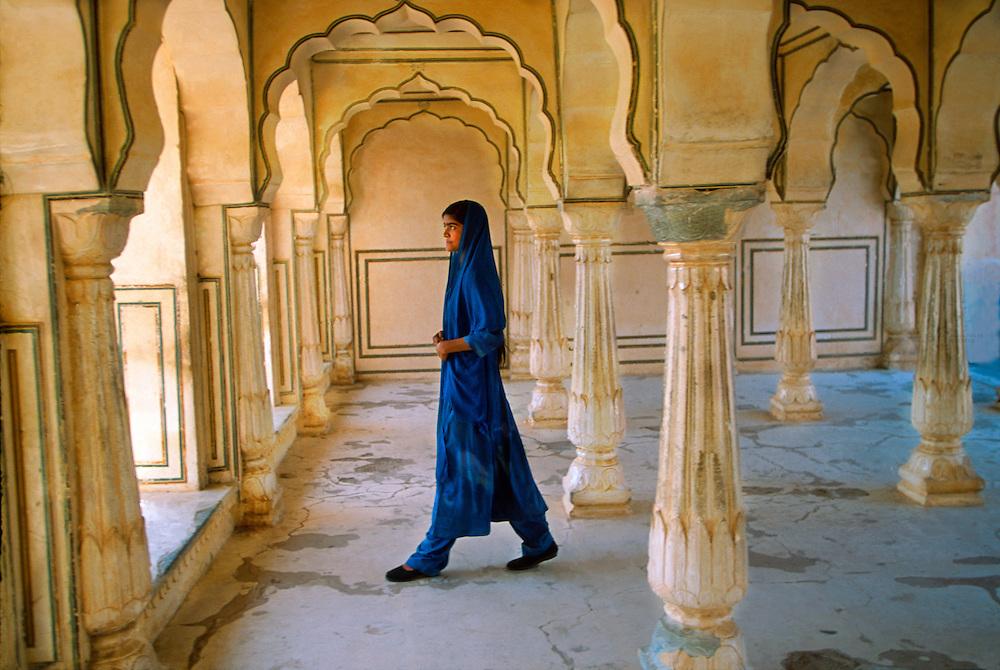 Rajasthani woman walking through arches at the Amber Fort and Palace, near Jaipur, Rajasthan, India