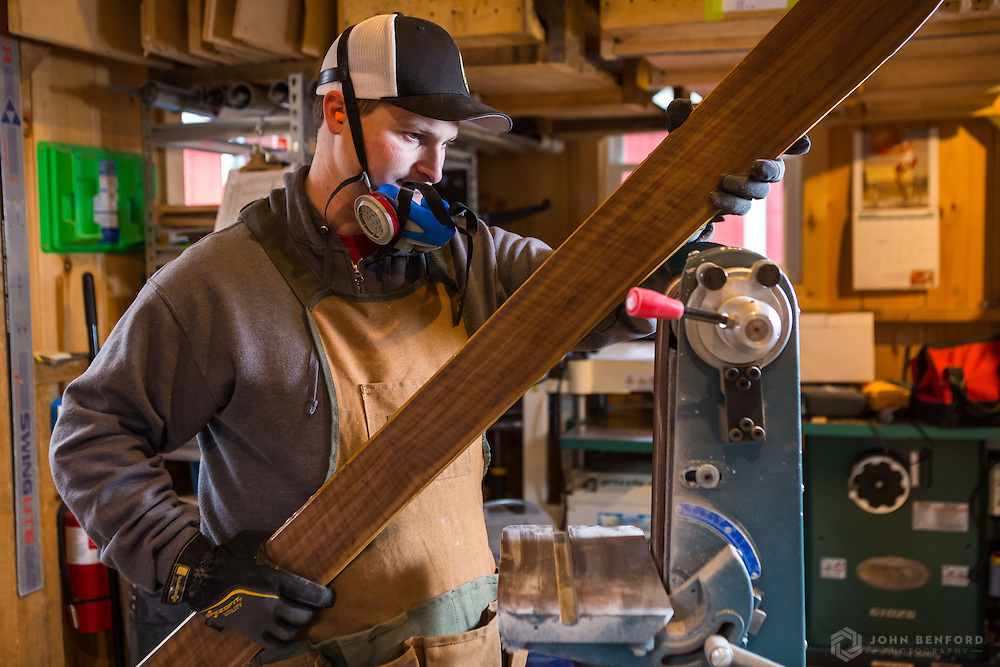 EJ prepares to sand the metal edge of the ski on a belt sander. The process produces significant dust and sparks, so breathing masks and eye protection are used along with an overhead air filter.