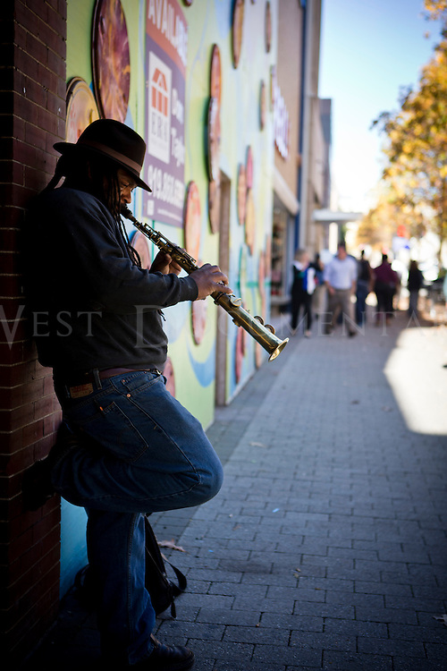"""Freddy Greene, of Raleigh, plays his 98-year-old soprano saxophone, """"Lucy"""", which he has owned for the last 20 years, on Fayetteville Street, downtown Raleigh, November 19, 2013."""