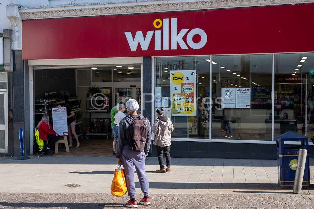 A member of staff sits by a health warning sign about social distancing and COVID-19 outside the entrance to Wilko on the 10th of April 2020, in Folkestone, United Kingdom. All essential business's  including shops that sell food and cleaning products are still operating during the Corona virus outbreak now have strict health guidelines regarding COVID-19 for all people entering the premises regarding social distancing.