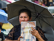 22 OCTOBER 2016 - BANGKOK, THAILAND: A mourner with a portrait of the Bhumibol Adulyadej, the King of Thailand, sits in the rain on Sanam Luang in Bangkok. Sanam Luang, the Royal Ceremonial Ground, was packed Saturday with more than 100,000 people mourning the Monarch's death. The King died Oct. 13, 2016. He was 88. His death came after a period of failing health. Bhumibol Adulyadej was born in Cambridge, MA, on 5 December 1927. He was the ninth monarch of Thailand from the Chakri Dynasty and is also known as Rama IX. He became King on June 9, 1946 and served as King of Thailand for 70 years, 126 days. He was, at the time of his death, the world's longest-serving head of state and the longest-reigning monarch in Thai history.       PHOTO BY JACK KURTZ