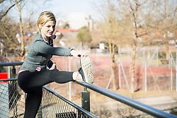 Woman in sportswear stretching outdoors