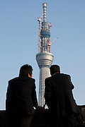 Salarymen or japanese office workers take in the view of the Tokyo Sky Tree under construction.  When finished this telecommunications towewr will measure 634 metres from top to bottom making it the tallest structure in East Asia. Oshiage, Tokyo, Japan. February 4th 2011