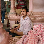 A shopkeeper in the busy Chadni Chowk market. Pink color.