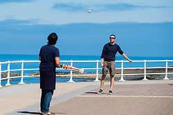 ©Licenced to London News Pictures.<br /> Aberystwyth, UK. 22/07/2018. Young men play an impromptu game of cricket on the promenade  in Aberystwyth on a gloriously sunny Sunday morning in west wales. The UK wide heatwave continues, with no respite from the very dry weather and temperatures are expected to exceed 30ºc again by the end of the week. Photo credit: Keith Morris/LNP