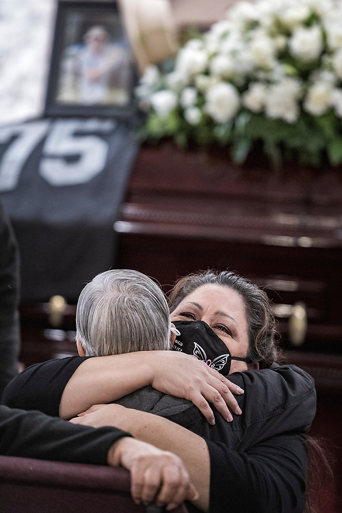Rochelle Ponce Ybarra comforts Roberta Martinez during the funeral for her sister Carmelita Martinez at Pastor El Buen church in San Jose, Calif. on Feb. 3, 2021.