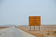 Warning sign in Hebrew, Arabic and English Caution! Tanks crossing and dust clouds. Photographed in The Negev Desert, Israel on the way to Eilat