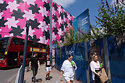 Blue hoarding around the construction site where a new high rise development, the Beorma Quarter, will be situated near the iconic Selfridges building on 14th July 2021 in Birmingham, United Kingdom. This site, part of the city centre redevelopment has stalled in recent months and currently sits quiet and with plants overgrowing its graffiti covered perimeter.