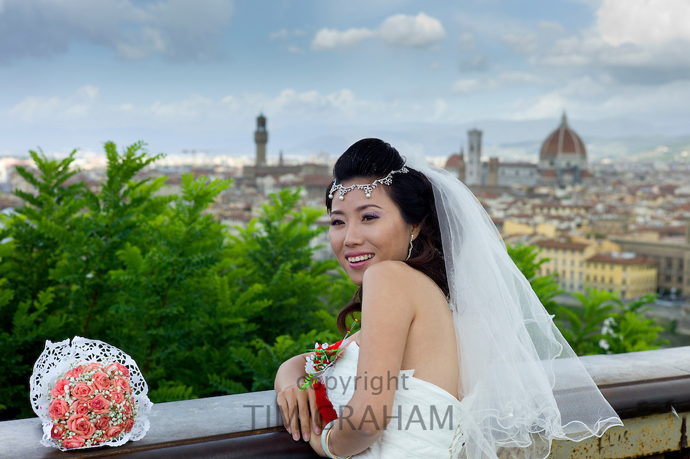 Chinese bridge poses for photograph with backdrop of The City of Florence,  Tuscany, Italy