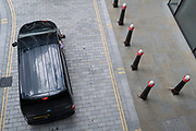 As workers in London largely remain working from home during the Coronavirus pandemic, a driver whose elbow rests on his vehicle's door queues in traffic an urban street landscape of road markings and traffic bollards in the City of London, the capital's financial district, on 4th September 2020, in London, England.
