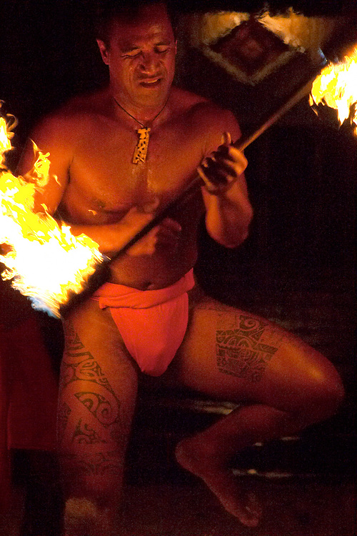 Exotic native fire dancer in performance at the Tiki Village on Moorea, Society Islands, French Polynesia